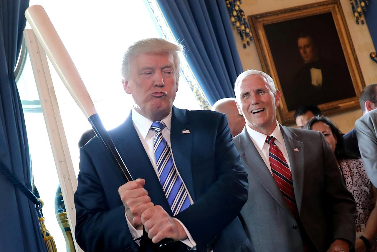FILE PHOTO: Vice President Mike Pence laughs as U.S. President Donald Trump holds a baseball bat as they attend a Made in America product showcase event at the White House in Washington, U.S., July 17, 2017. REUTERS/Carlos Barria/File Photo