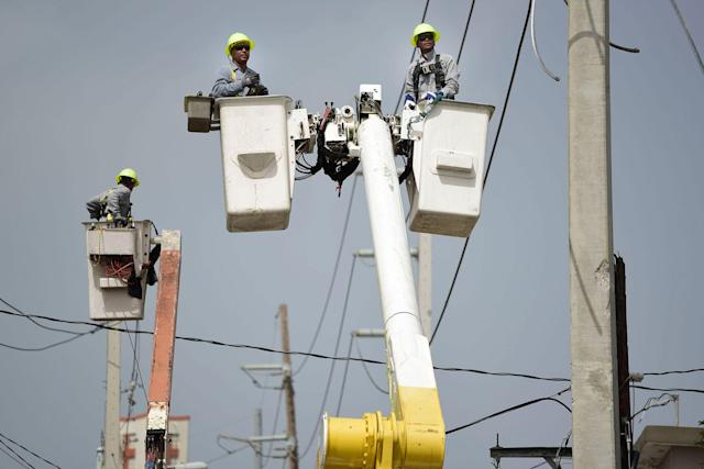 <p>A brigade from the Electric Power Authority repairs distribution lines damaged by Hurricane Maria in the Cantera community of San Juan, Puerto Rico on Oct. 19, 2017. The storm struck after the Authority had filed for bankruptcy in July, put off maintenance and had finished dealing with outages from Hurricane Irma. (Photo: Carlos Giusti/AP) </p>