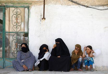Women sit in front of their home in the border town of Jarablus, Syria. REUTERS/Umit Bektas