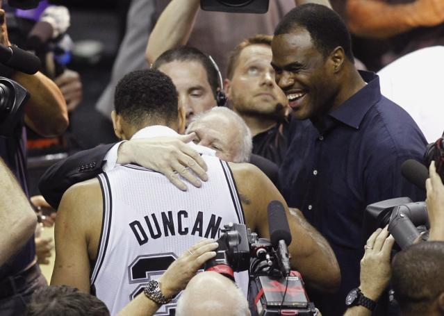San Antonio Spurs' Tim Duncan (L) hugs coach Gregg Popovich as former Spurs champion David Robinson (R) looks on after the Spurs defeated the Miami Heat in Game 5 of their NBA Finals basketball series in San Antonio, Texas, June 15, 2014. REUTERS/Mike Stone (UNITED STATES - Tags: SPORT BASKETBALL)
