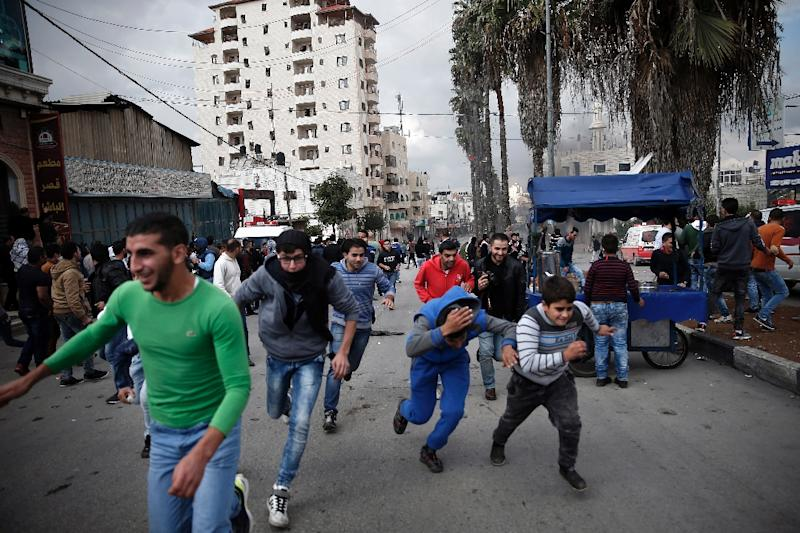 Palestinian demonstrators run for cover as Israeli security forces fire tear gas during clashes in the West Bank city of Hebron, in October 2015