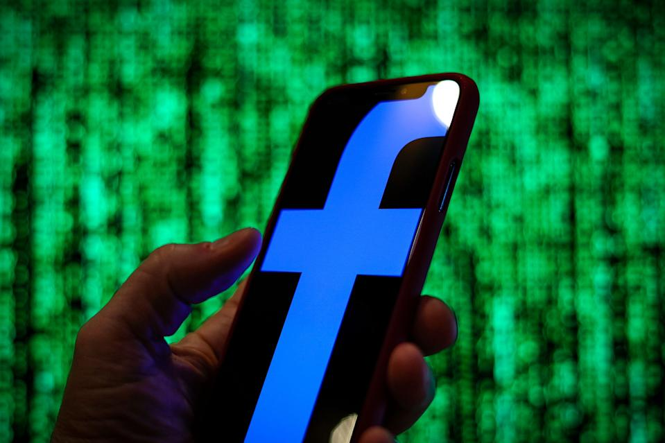 The Facebook logo is seen displayed on a mobile device in front of a screen with data in this photo illustration in Warsaw, Poland on March 19, 2019. (Photo by Jaap Arriens/NurPhoto via Getty Images)