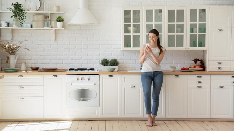Happy woman surfing net on mobile standing barefoot on warm floor in Scandinavian kitchen. Young housewife in her 20s shopping online using smartphone leaning on modern kitchen countertop and smiling