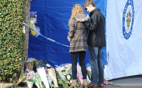 Lydia Wilkinson, the daughter of stabbing victims Peter and Tracey Wilkinson, views floral tributes with her boyfriend at her family home in Stourbridge - Credit: Rui Vieira/PA