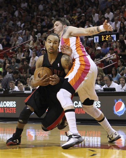 Toronto Raptors' Jerryd Bayless, left, drives around Miami Heat's Mike Miller (13) in the second half of an NBA basketball game in Miami, Sunday, Feb. 5, 2012. The Heat won 95-89. (AP Photo/Alan Diaz)