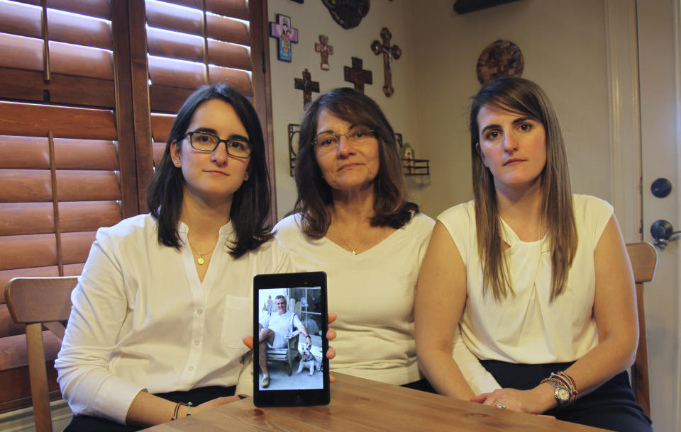 Dennysse Vadell sits between her daughters Veronica, right, and Cristina holding a digital photograph of father and husband Tomeu who is currently jailed in Venezuela, in Katy, Texas on Feb. 15, 2019 , (John L Mone/AP)