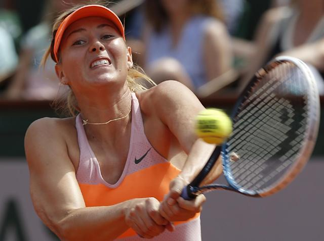 Russia's Maria Sharapova returns the ball to Romania's Simona Halep during their final match of the French Open tennis tournament at the Roland Garros stadium, in Paris, France, Saturday, June 7, 2014. (AP Photo/Michel Euler)