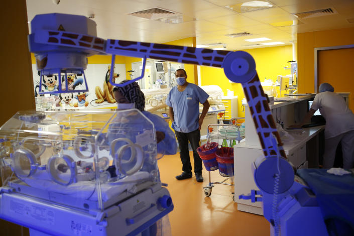 Paediatrician Dr. Msayif Khali supervises the operation as a nurse takes care of one of the nine babies protected in an incubator at the maternity unit of the Ain Borja clinic in Casablanca, Morocco, Thursday May 20, 2021, two weeks after Mali's Halima Cisse, 25, gave birth to nine healthy babies. (AP Photo / Abdeljalil Bounhar)