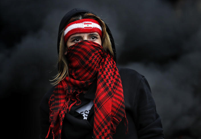 A protester covers her face by a scarf, as she blocks a main highway, during a protest in the town of Zouk Mosbeh, north of Beirut, Lebanon, Monday, March 8, 2021. The dayslong protests intensified Monday amid a crash in the local currency, increase of consumer goods prices and political bickering between rival groups that has delayed the formation of a new government. (AP Photo/Hussein Malla)