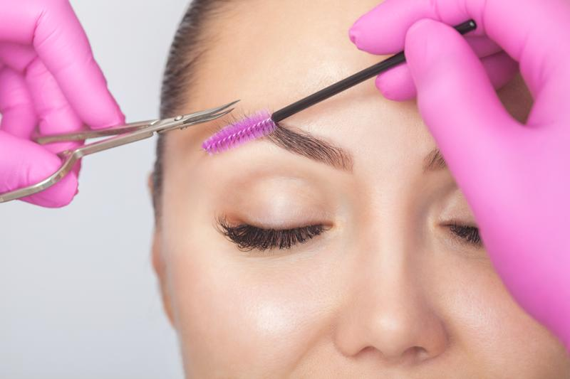 The make-up artist cuts eyebrows with scissors. A girl with beautiful long eyelashes and well-groomed eyebrows. Cosmetology concept