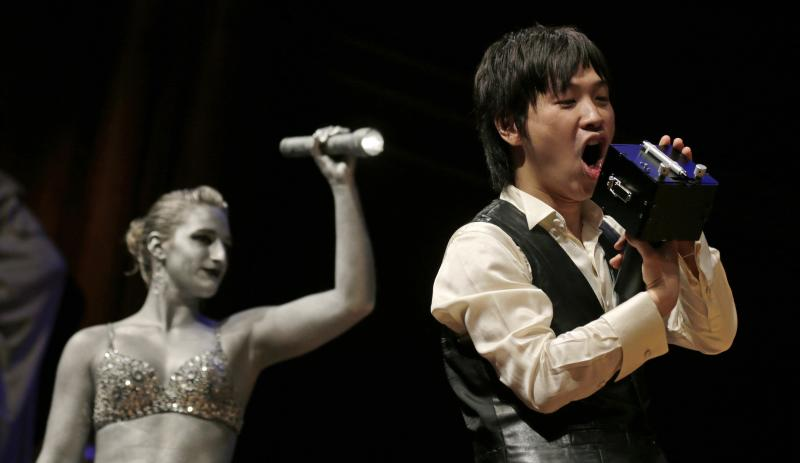 """Koji Tsukada yells into his invention the """"SpeechJammer"""" during a performance at the Ig Nobel Prize ceremony at Harvard University, in Cambridge, Mass., Thursday, Sept. 20, 2012. The Ig Nobel prize is an award handed out by the Annals of Improbable Research magazine for silly sounding scientific discoveries that often have surprisingly practical applications. (AP Photo/Charles Krupa)"""