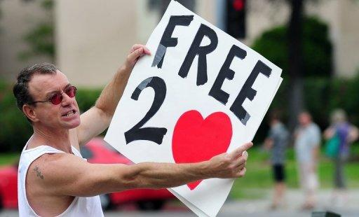 "A protester holds a placard for passing traffic on Sunset Boulevard in Hollywood in front of a Chick-fil-A fast food restaurant. Gays and lesbians puckered up at ""kiss-ins"" outside Chick-fil-A outlets across the United States in protest over the fast-food chain's opposition to same-sex marriage"
