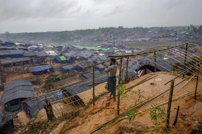 """-FILE- In this Wednesday, Sept. 20, 2017, file photo A Rohingya Muslim man, who crossed over from Myanmar into Bangladesh, builds a shelter for his family in Taiy Khali refugee camp, Bangladesh. Gambia has filed a case at the United Nations' highest court in The Hague, Netherlands, Monday, Nov. 11, 2019, accusing Myanmar of genocide in its campaign against the Rohingya Muslim minority. A statement released Monday by lawyers for Gambia says the case also asks the International Court of Justice to order measures """"to stop Myanmar's genocidal conduct immediately."""" (AP Photo/Dar Yasin, file)"""