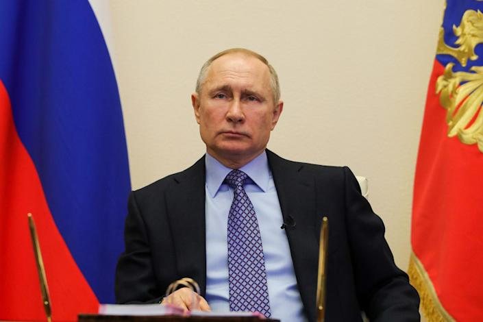Vladimir Putin attends a meeting with regional officials via tele link in his residence on March 30
