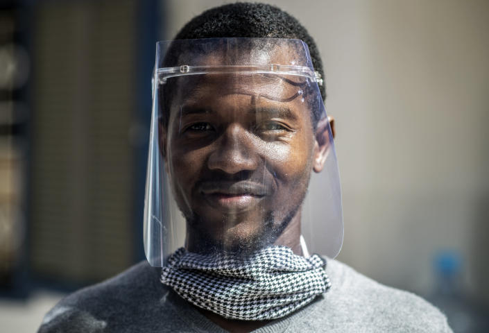 In this photo taken Thursday, April 16, 2020, Idrissa Sall demonstrates a protective face shield made with a laser cutter, to be used to protect against transmission of the coronavirus, at the FabLab workshop at the Ker Thiossane multimedia center in Dakar, Senegal. Researchers across Africa are looking for ways to make their own ventilators, protective equipment and hand sanitizers as the continent faces a peak in coronavirus cases long after the United States and European countries have bought up global supplies during the pandemic. (AP Photo/Sylvain Cherkaoui)