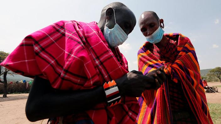 Maasai elders use a mobile phone at their homestead within the Orboma Manyatta in Sekenani near the Maasai Mara game reserve in Narok County