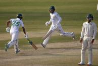 Pakistan's Faheem Ashraf, center, and Fawad Alam, left, run between the wicket while South Africa's Aiden Markram watches during the second day of the first cricket test match between Pakistan and South Africa at the National Stadium, in Karachi, Pakistan, Wednesday, Jan. 27, 2021. (AP Photo/Anjum Naveed)