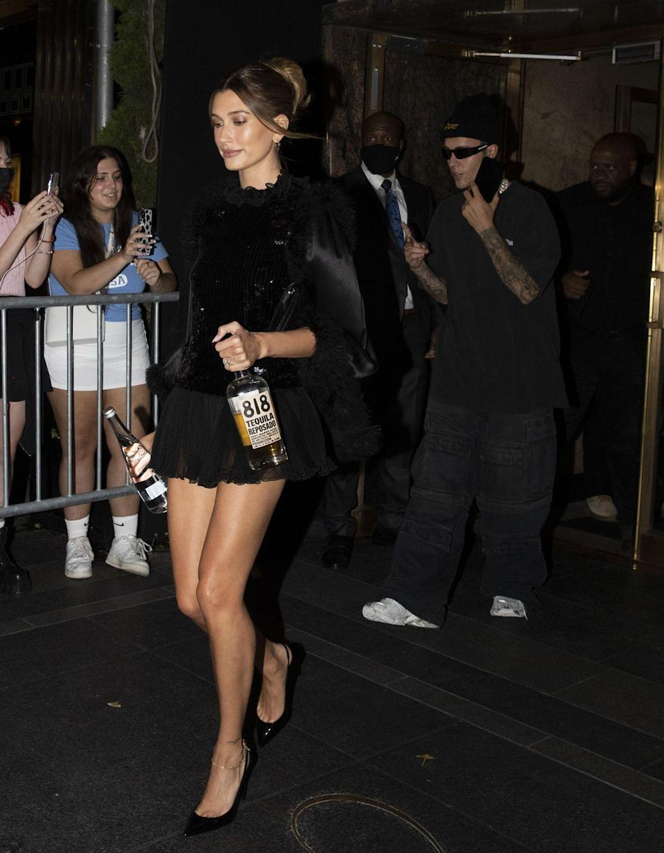 <p>Hailey carried a bottle of friend Kendall Jenner's tequila brand 818 into the party, wearing a black mini dress.</p>