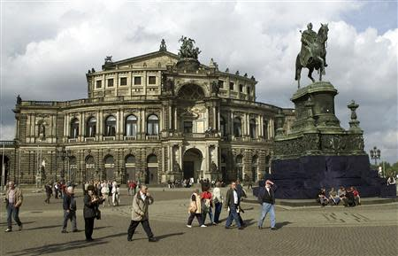 People walk past a statue of King Johann of Saxony (1801-73) in front of the Semperoper opera house in Dresden in this October 2, 2000 file photo. REUTERS/Arnd Wiegmann/Files