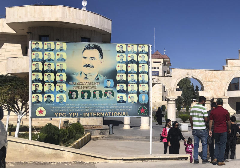 People pass a giant banner with a portrait of jailed leader of the Kurdistan Workers' Party, or PKK, Abdullah Ocalan, center, with other portraits of killed Kurdish fighters, set at the border crossing between Iraq and Syria's Kurdish-held, in Semelka, northeast Syria, Monday Oct. 14, 2019. (AP Photo/Hussein Malla)