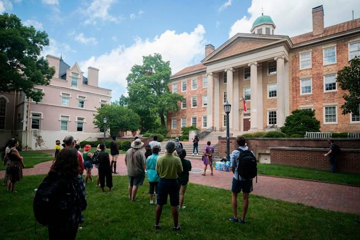A small crowd of UNC-Chapel Hill students and staff gather outside South Building in Chapel Hill, N.C. for a demonstration, put on by the UNC chapter of the NAACP on Monday, July 12, 2021, in solidarity with students who protested a recent board of trustees meeting.