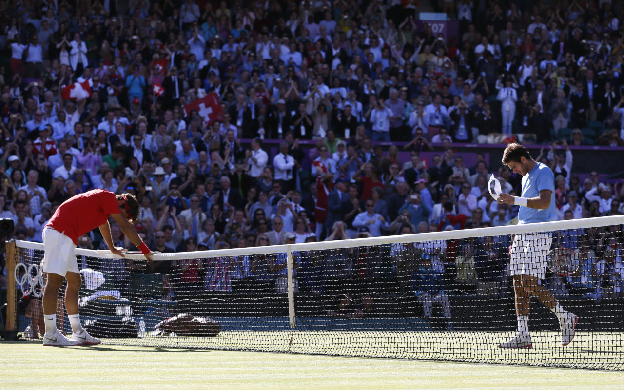 Switzerland's Roger Federer rests on the net after winning his men's singles tennis semi-final match against Argentina's Juan Martin del Potro (R) at the All England Lawn Tennis Club during the London 2012 Olympic Games August 3, 2012.            REUTERS/Stefan Wermuth (BRITAIN  - Tags: OLYMPICS SPORT TENNIS)