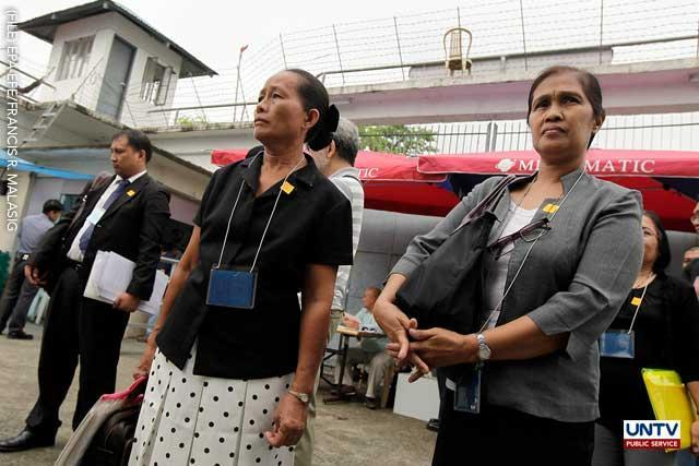 Filipinos Juliet Evardo (R) and Editha Tiamson (2-R), relatives of victims of the Maguindanao massacre, enter a prison facility to attend the on-going hearing at a maximum security prison in Taguig, south of Manila, Philippines, on 25 May 2011.