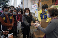 FILE - In this Feb. 7, 2020, file photo, people queue up to buy face masks in Hong Kong. Fear of the spreading coronavirus has led to a global run on sales of face masks despite medical experts' advice that most people who aren't sick don't need to wear them. (AP Photo/Kin Cheung, File)