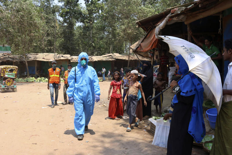 FILE - In this April 15, 2020, file photo, a health worker from an aid organization walks wearing a hazmat suit at the Kutupalong Rohingya refugee camp in Cox's Bazar, Bangladesh. Authorities in Bangladesh on Tuesday, June 2, confirmed the first death of a Rohingya refugee amid rising cases of new infections in the sprawling camps in the South Asian country where more than 1 million Rohingya Muslims have been sheltered after fleeing from neighboring Myanmar, according to a doctor and the United Nations. The 71-year-old refugee died Saturday at Ukhiya in Cox's Bazar, but samples collected from him proved positive on Monday, said Abu Toha M.R. Bhuiyan, chief health coordinator of the office of Refugee, Relief and Repatriation Commissioner. (AP Photo/Shafiqur Rahman, File)