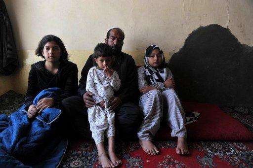 Afghan girl Tarana Akbari (right) sits with her father and siblings after an interview with an AFP reporter at their home in Kabul. Down a rutted dirt alley in Old Kabul, Tarana -- the subject of AFP photographer Massoud Hossaini's Pulitzer-winning photograph -- says she still has nightmares about the day a suicide bomber made her image world famous