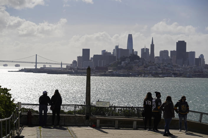 People look out at the views of the skyline and bay from Alcatraz Island in San Francisco, Monday, March 15, 2021. The historic island prison was reopened to visitors Monday after being closed since December because of the coronavirus threat. Visitors were also able to tour the inside of the main cell house for the first time in a year. (AP Photo/Eric Risberg)
