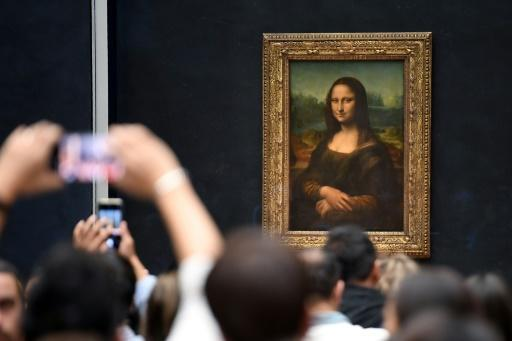 Visitors take pictures in frront of Mona Lisa