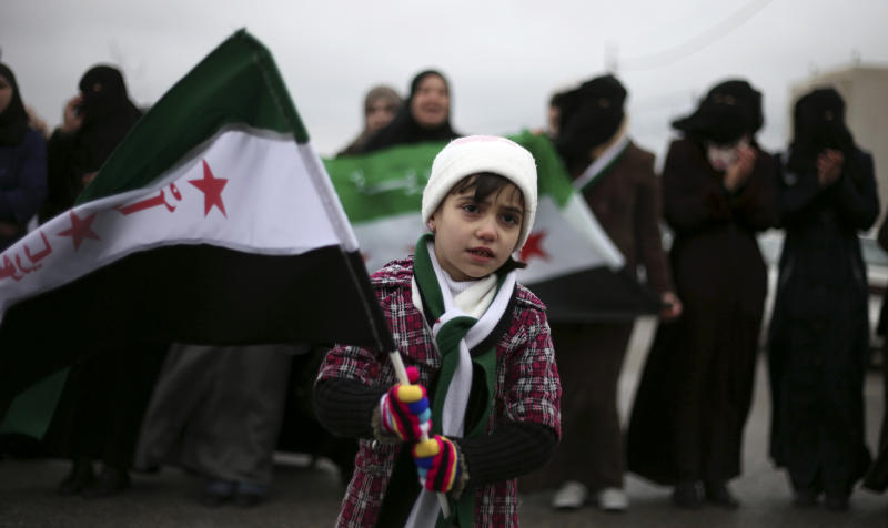 "A girl waves the revolutionary Syrian flag during a protest against President Bashar Assad in front of the Syrian embassy to commemorate the 31st anniversary of the 1982 Hama massacre, in the era of Hafez Assad, in Amman, Jordan, Friday, Feb. 1, 2013. The Arabic writing on the flag reads ""free Syria."" (AP Photo/Mohammad Hannon)"