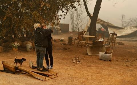 Krystin Harvey, left, comforts her daughter Araya Cipollini at the remains of their home in Paradise, Calif. - Credit: AP
