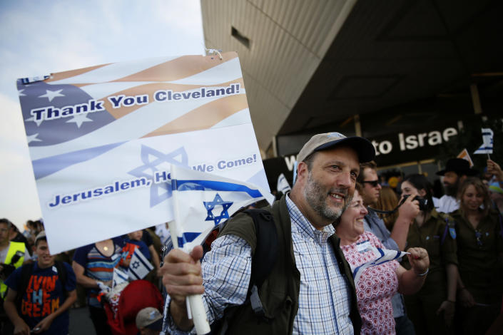 A Jewish immigrant from North America, who is making Aliyah (immigration to Israel) holds a sign and Israeli flag upon his arrival at Ben Gurion International airport on August 12, 2014, outside of Tel Aviv (AFP Photo/Gali Tibbon)