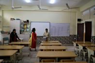 Teachers talk to each other in an empty classroom of a school after it remained closed on account of smog in New Delhi