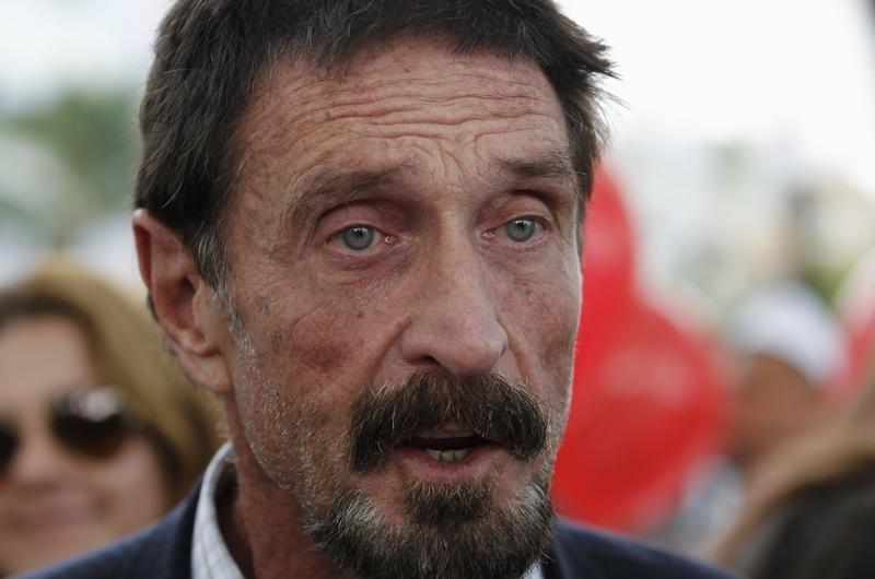 Computer software pioneer McAfee speaks with reporters outside his hotel in Miami Beach