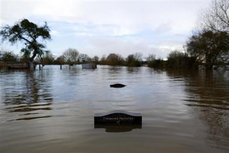 Gravestones are partially submerged in water in the flooded Somerset village of Moorland