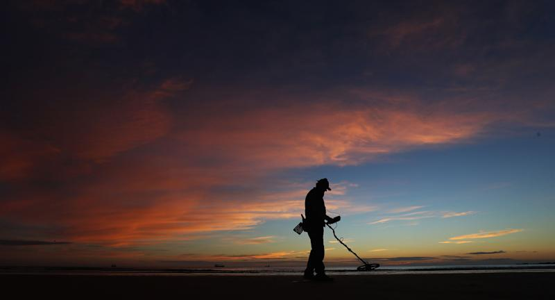 A man with a metal detector on Tynemouth Beach, Tyne and Wear, as dawn breaks.