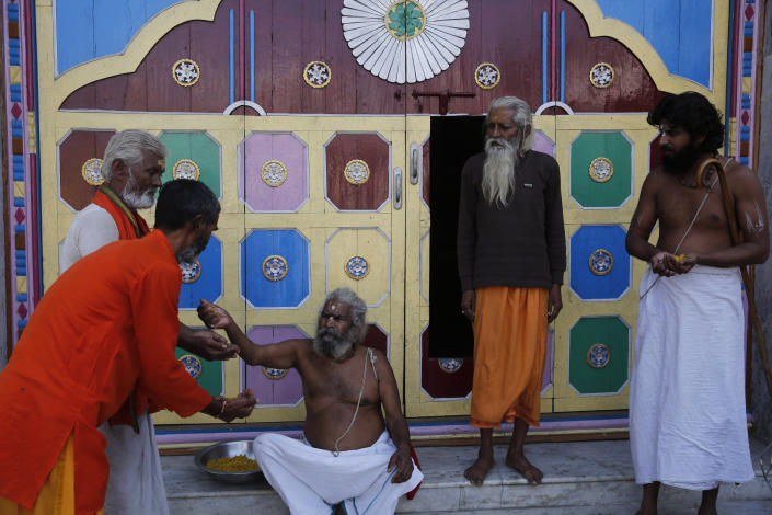 Hindu holy men celebrate the verdict in a decades-old land title dispute between Muslims and Hindus, in Ayodhya, India , Saturday, Nov. 9, 2019. India's Supreme Court on Saturday ruled in favor of a Hindu temple on a disputed religious ground and ordered that alternative land be given to Muslims to build a mosque. The dispute over land ownership has been one of the country's most contentious issues. (AP Photo/Rajesh Kumar Singh)