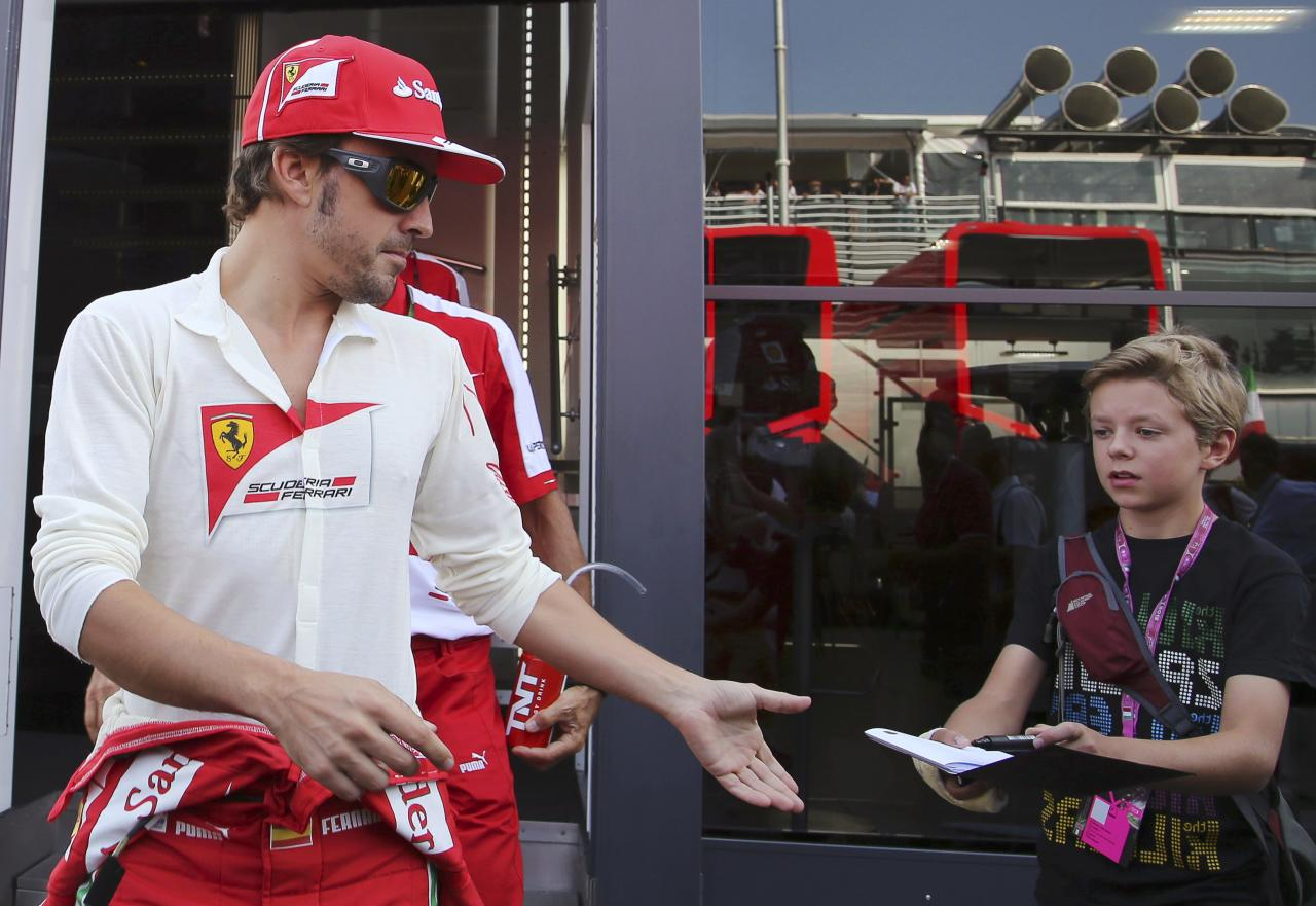 Ferrari Formula One driver Fernando Alonso (L) of Spain reaches out to sign an autograph before the start of the qualifying session of the Italian F1 Grand Prix at the Monza circuit September 7, 2013. REUTERS/Enrico Schiavi (ITALY - Tags: SPORT MOTORSPORT F1)