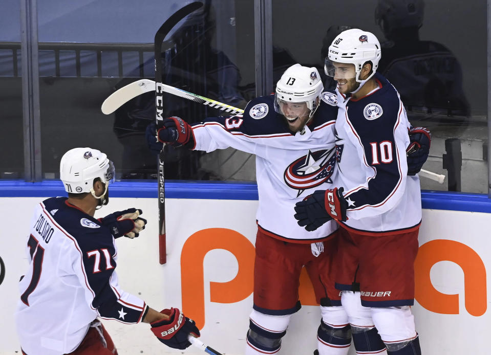 Columbus Blue Jackets right wing Cam Atkinson (13) celebrates his goal with Alexander Wennberg (10) and Nick Foligno (71) during the third period of an NHL hockey playoff game against the Toronto Maple Leafs in Toronto, Sunday, Aug. 2, 2020. (Nathan Denette/The Canadian Press via AP)
