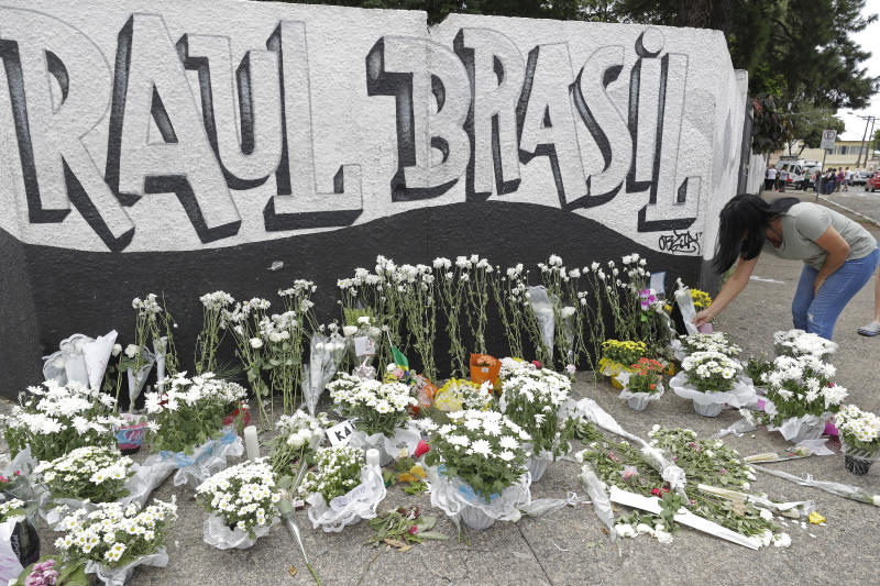 A woman leaves flowers one day after a mass, school shooting outside the Raul Brasil state school in Suzano, Brazil, Thursday, March 14, 2019. Classmates, friends and families began saying goodbye on Thursday, with thousands attending a wake in the Sao Paulo suburb while authorities worked to understand what drove two former students to attack the Raul Brasil State School with a gun, crossbows and small axes. (AP Photo/Andre Penner)