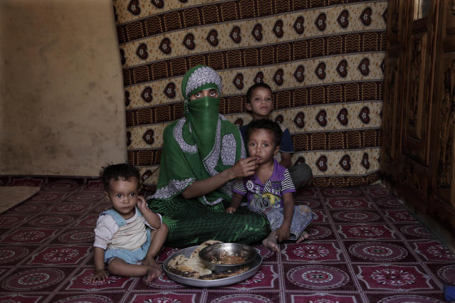 "<p>In this Feb. 11, 2018 photo, Sherine, feeds her children scraps of bread dipped in ""besbas,"" a sauce of tomato and garlic in their mud house in al-Mallah, Yemen. The sharp bones of her face creasing her green veil and her thin body showed otherwise. Her 1-year-old daughter Amal, has been diagnosed with acute malnutrition and can't support herself on her legs. Her 3-year-old son had malnutrition as a toddler. (Photo: Nariman El-Mofty/AP) </p>"
