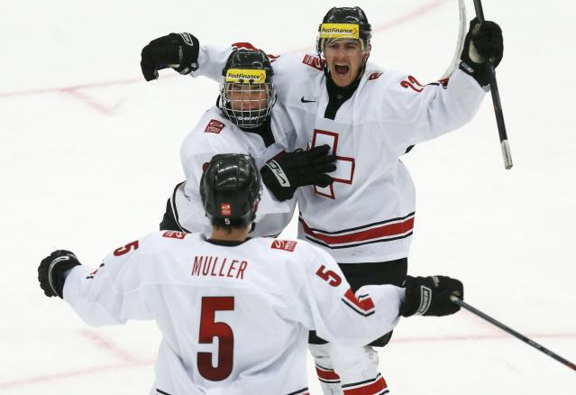 Switzerland's Nico Dunner (R) celebrates his goal against Canada with teammate Kevin Fiala and Mirco Muller (5) during the second period of their IIHF World Junior Championship ice hockey game in Malmo, Sweden, January 2, 2014. REUTERS/Alexander Demianchuk (SWEDEN - Tags: SPORT ICE HOCKEY)