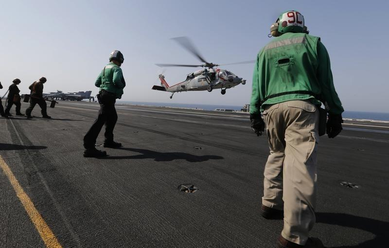 A MH-60S lands on flight deck as crew prepares to receive it onboard the aircraft carrier USS George H.W. Bush, in the Gulf