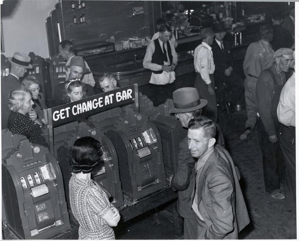 <p>Small crowds of people try their luck at the slot machines inside a cheap Las Vegas bar.</p>