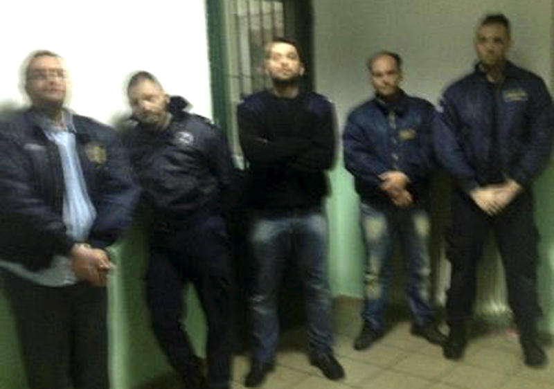 This photo taken by an unnamed prisoner with a cellphone shows hostages, both prison officers and prisoners, being held by Albanian convict Alket Rizaj at Malandrino prison, in central Greece, on Saturday, March 16, 2013. Rizaj is demanding to be allowed to leave the prison, claiming to be heavily armed. Police special forces have deployed outside the prison, while prison officers, Rizaj's lawyer, and a prosecutor try to negotiate with him. (AP Photo)