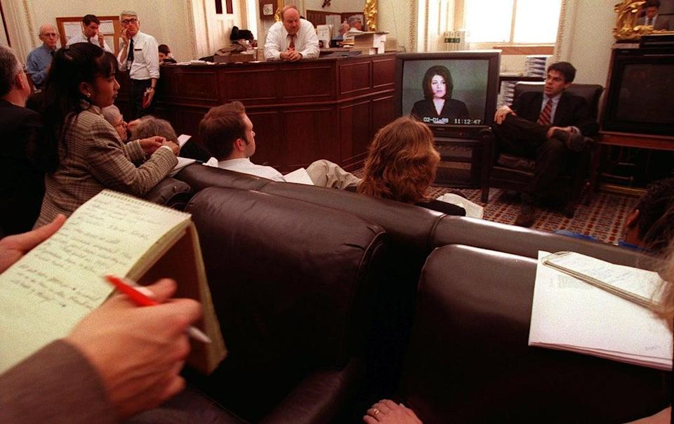 Reporters in a press room in the US Capitol watch as the videotaped testimony of Monica Lewinsky is played in the US Senate during the impeachment trial of President Bill Clinton on 6 February 1999 (MARIO TAMA/AFP via Getty Images)