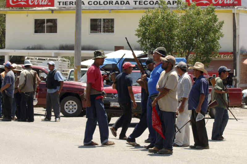A group of armed vigilantes stand at the entrance to the town of Tierra Colorada, Mexico, Tuesday March 26, 2013. Hundreds of armed vigilantes have taken control of this town, which lies on a major highway in the Pacific coast state of Guerrero, arresting local police officers and searching homes after one of their vigilante leaders was killed. (AP Photo/Alejandrino Gonzalez)